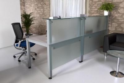 Recepción de cristal en dos modulos - Recepción de cristal compuesta de 2 módulos unidos. Las mesas de oficina que componen la linea de mobiliario Exe Cuadra combinan el metal cromado o pintado con las superficies de cristal translucido (10 mm. de grosor) de melamínico en haya, gris o wengue.Las patas de las mesas disponen de regulación de altura de 2 cm. fabricado en tubo de acero de 6 x 6 cm. cromado o pintado en blanco o en color aluminio.La combinación de la superficie en cristal y las patas cromadas le dan a esta linea de mobiliario de oficina un diseño ligero, moderno y actual que le sorprenderá a sus visitantes.