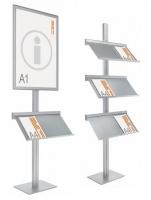 Expositores de información con peana - Expositores de información. Conjunto formado por un portapósters de formato DIN A1, a una o dos caras y portaestantes metálico gris sobre perfil vertical de aluminio anodizado en plata mate.