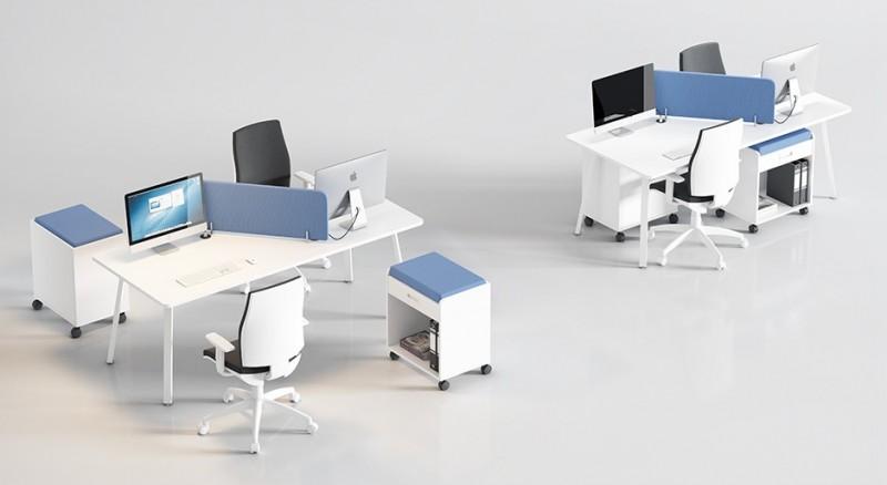 Puesto de trabajo en isla con separación tapizada - Los puestos de trabajo operativos también se pueden crear con una sola mesa de oficina con un biombo de separación, maximizamos el espacio sin perder comodidad.  A las cajoneras con ruedas se les puede acoplar (cono se ve en la foto) un cojín para que sirvan de asiento.